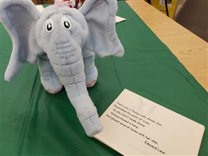 Elephant with poem sitting on a table.