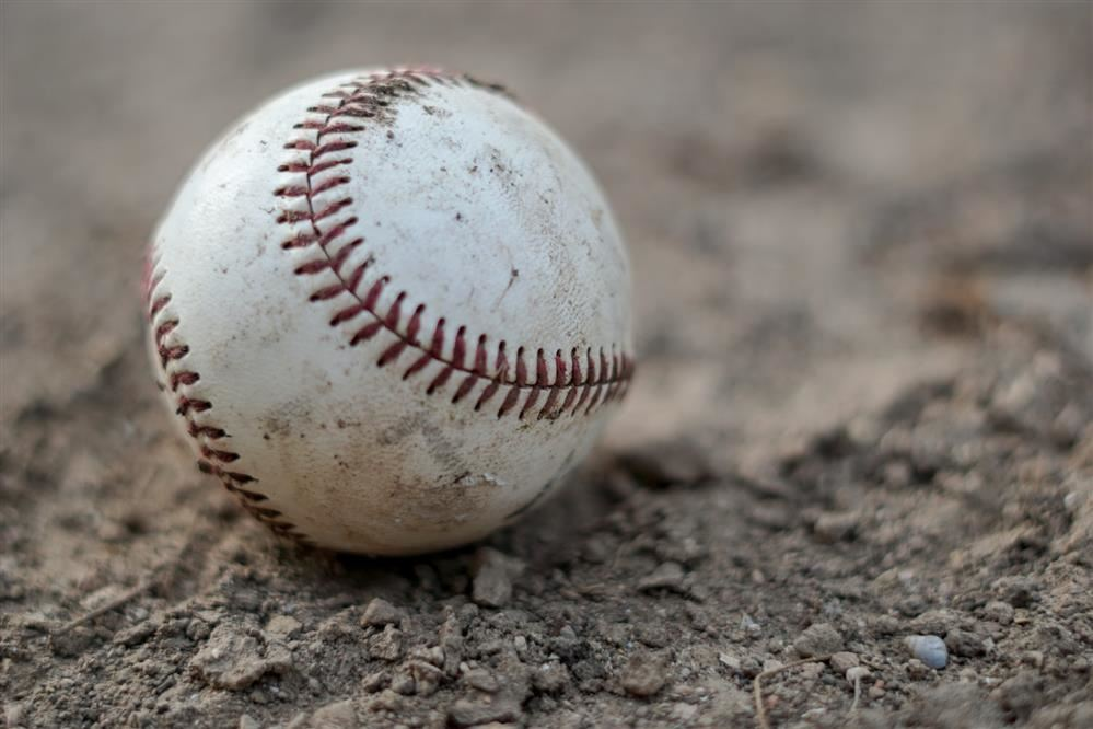 baseball in dirt. image by Thomas Park on Unsplash