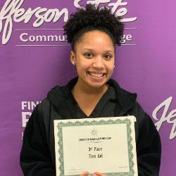 Kayla Fower poses in front of the Jefferson State Community College backdrop with her certificate.