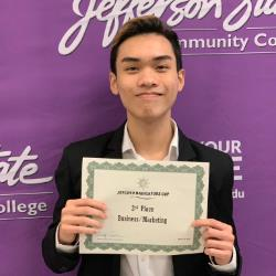 Khoi Nguyen poses in front of the Jefferson State Community College backdrop with his certificate.